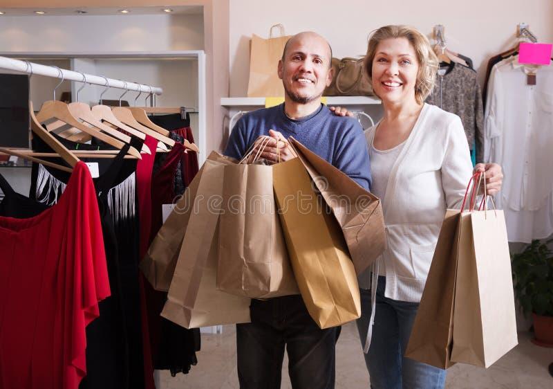 Ehemann, welche seiner Frau hilft, Kleidung zu wählen lizenzfreies stockbild