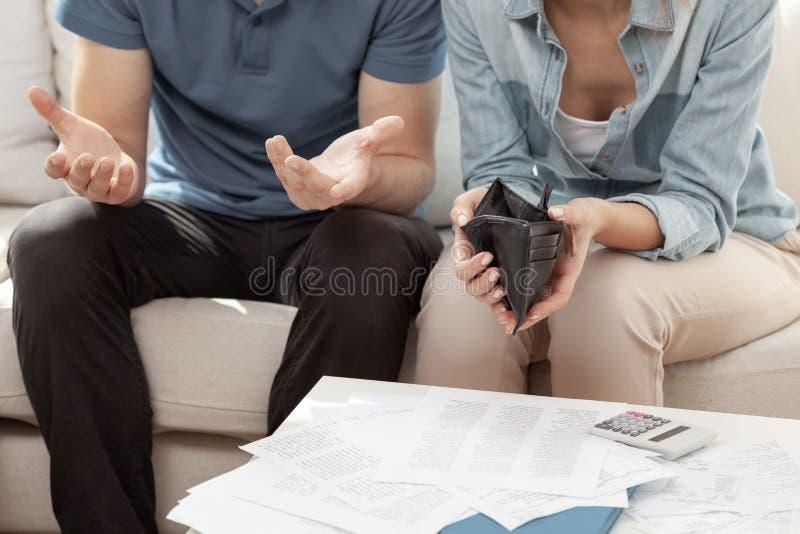 Ehepaar, das im Wohnzimmer mit leerer Wand und einem Haufen Rechnungen sitzt lizenzfreie stockfotos