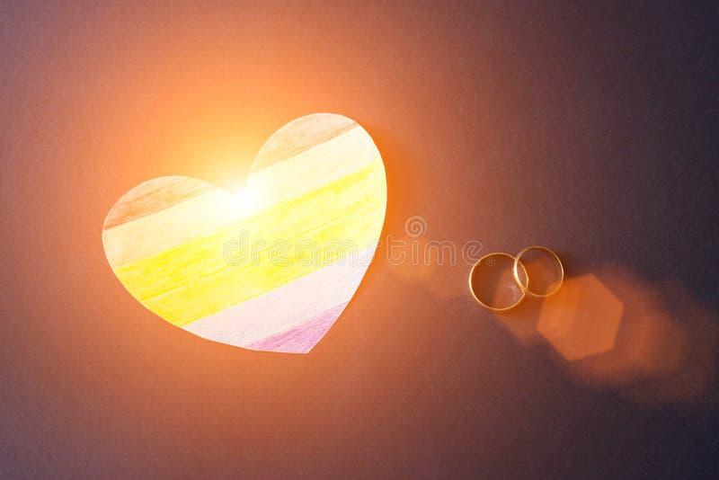 Eheringe auf einem blauen Hintergrund und einem Herzen in Form eines Flaggenlgbt, -homosexuellen Ehe und -sonne stockfoto