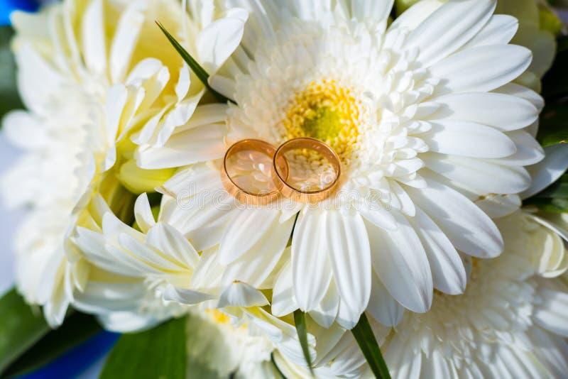 Eheringe auf einem Hochzeitsblumenstrauß stockbild