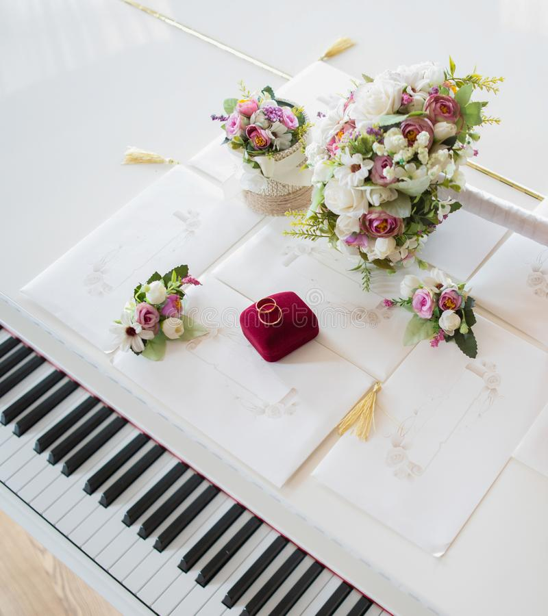 Eheringe auf einem weißen Klavier lizenzfreie stockfotos