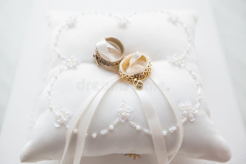 Eheringe auf weißem Kissen mit Spitze und Perlen lizenzfreie stockbilder