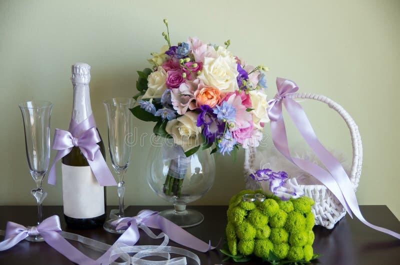 Eheringe, Blumenstrauß und Champagner stockbild