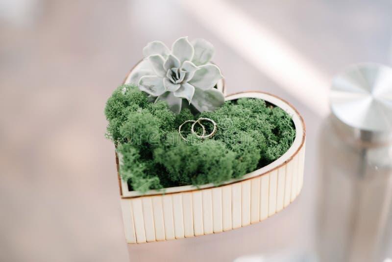 Eheringe der Braut und des Bräutigams sind in einer Holzkiste in Form eines Herzens stockbild