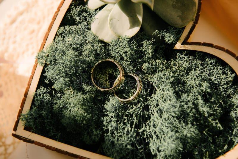 Eheringe der Braut und des Bräutigams sind in einer Holzkiste in Form eines Herzens stockfotos
