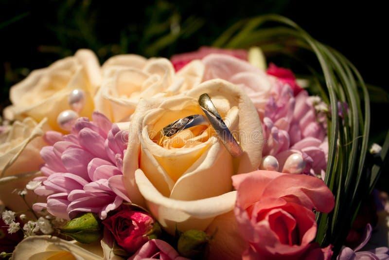Eheringe in einem Hochzeitsblumenstrauß lizenzfreie stockfotos