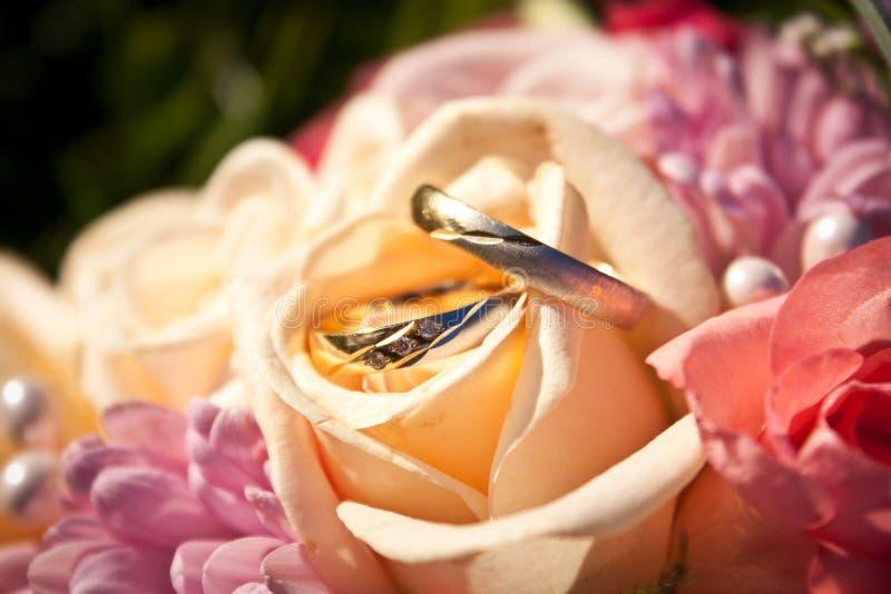 Eheringe in einem Hochzeitsblumenstrauß stockbild