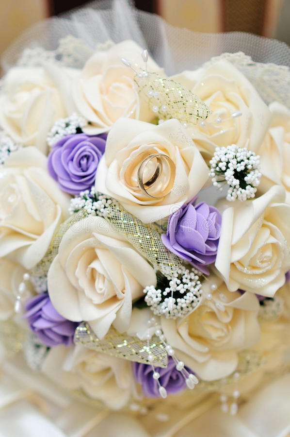 Eheringe auf dem Hochzeitsblumenstrauß lizenzfreie stockbilder