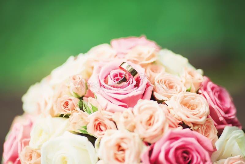 Eheringe mit Blumenstrauß, grüner Hintergrund lizenzfreie stockbilder