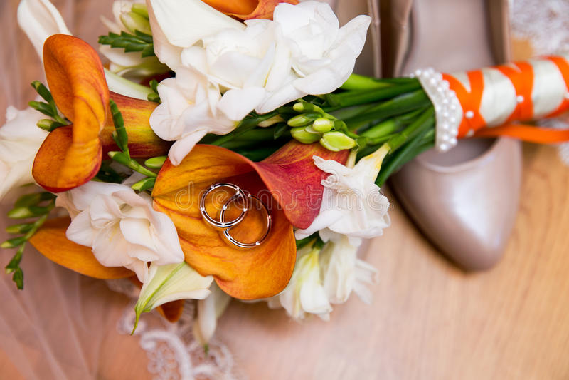 Eheringe mit Blumenstrauß und Schuhen stockbilder