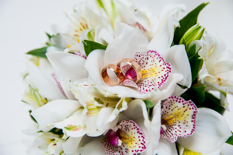 Eheringe mit Orchideenblumenstrauß lizenzfreie stockfotos