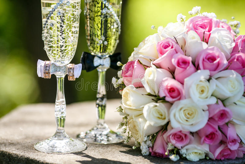 Eheringe mit Rosen und Gläsern Champagner stockbild