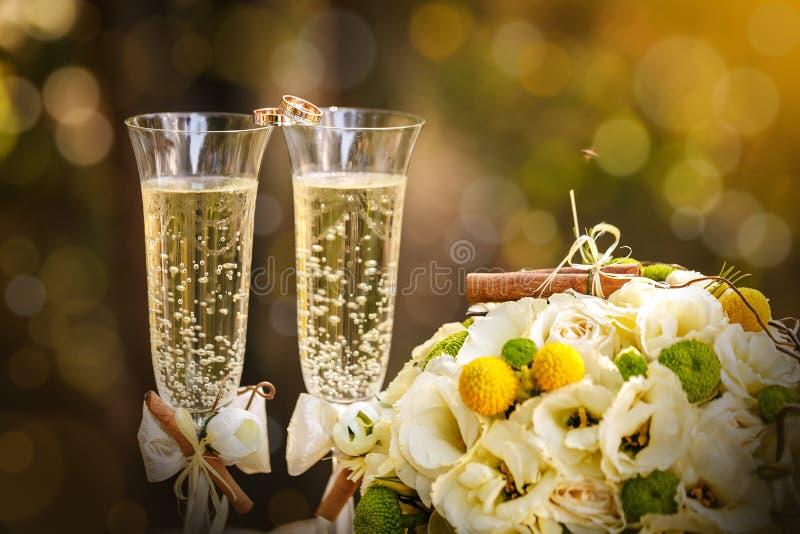 Eheringe mit Rosen und Gläsern Champagner lizenzfreie stockfotos