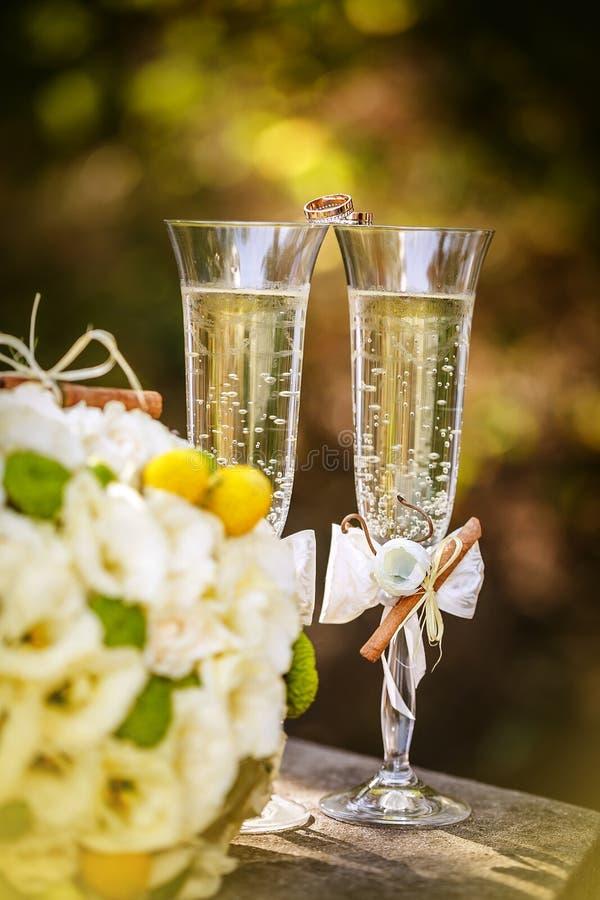 Eheringe mit Rosen und Gläsern Champagner lizenzfreies stockfoto