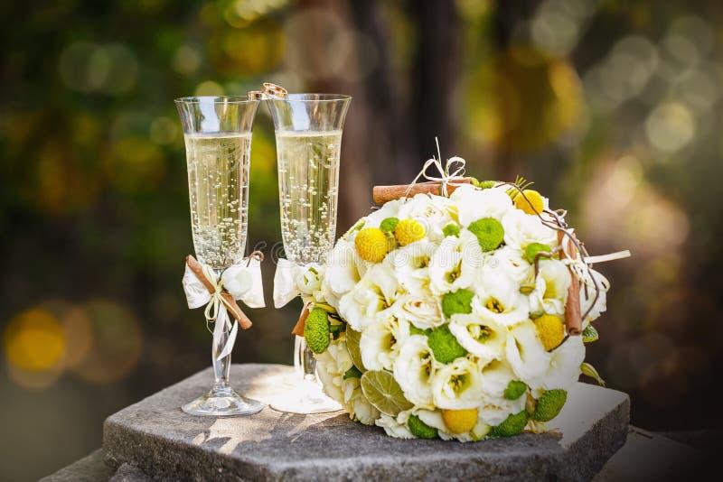 Eheringe mit Rosen und Gläsern Champagner stockfotos