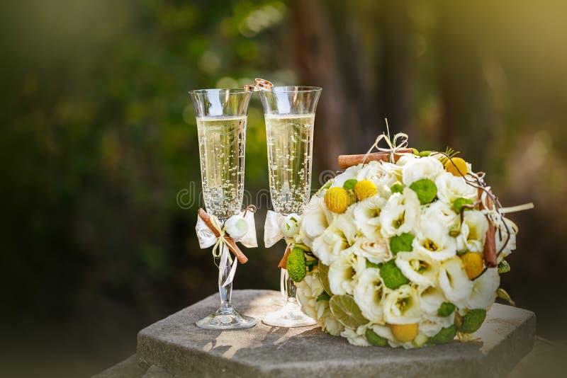 Eheringe mit Rosen und Gläsern Champagner stockfoto