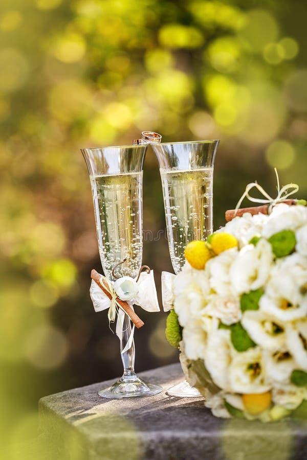 Eheringe mit Rosen und Gläsern Champagner stockfotografie