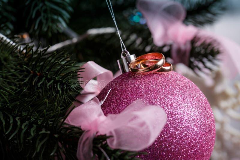 Eheringe, rosa Weihnachtsball, Weihnachtsbaum im Schnee stockfotos