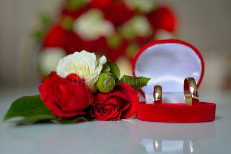 Eheringe, rote Rosen stockfoto