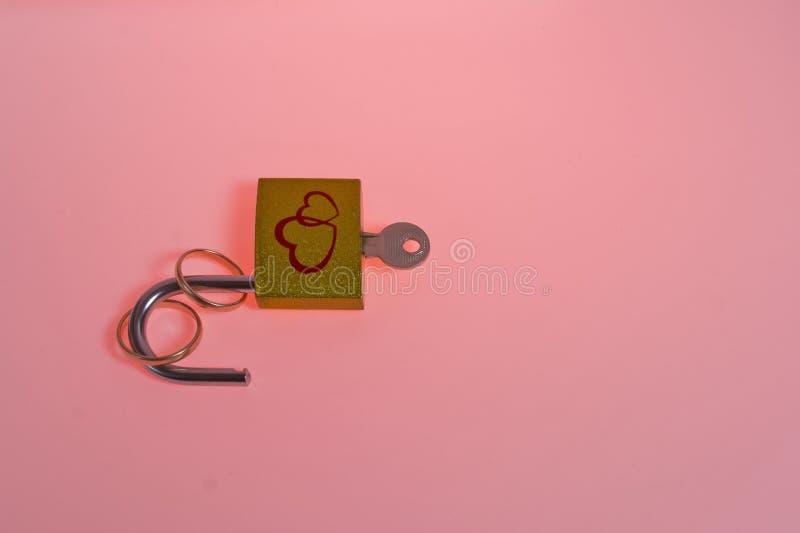 Eheringe, Schlüssel und offener Verschluss auf rosa Hintergrund mit Kopienraum stockfotografie