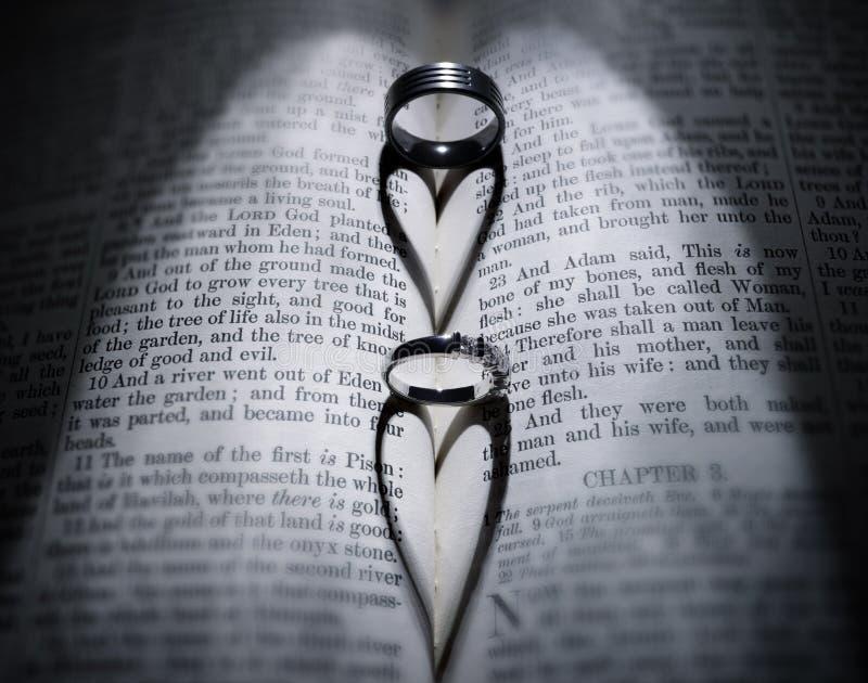 Eheringe und geformter Schatten des Herzens über Bibel stockfotos