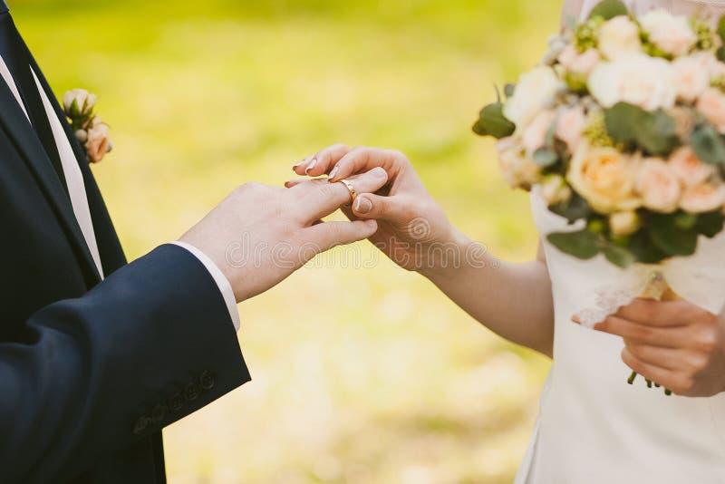 Eheringe und Hände der Braut und des Bräutigams stockfoto
