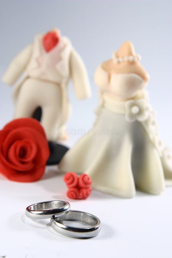 Eheringe und Miniaturpaar-Fondant-Kuchen lizenzfreie stockfotos