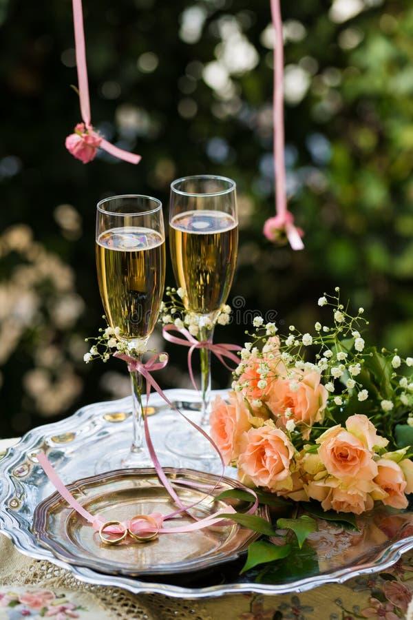 Eheringe vor der Zeremonie, mit verzierten Champagne-Gläsern und Rosen stockbild