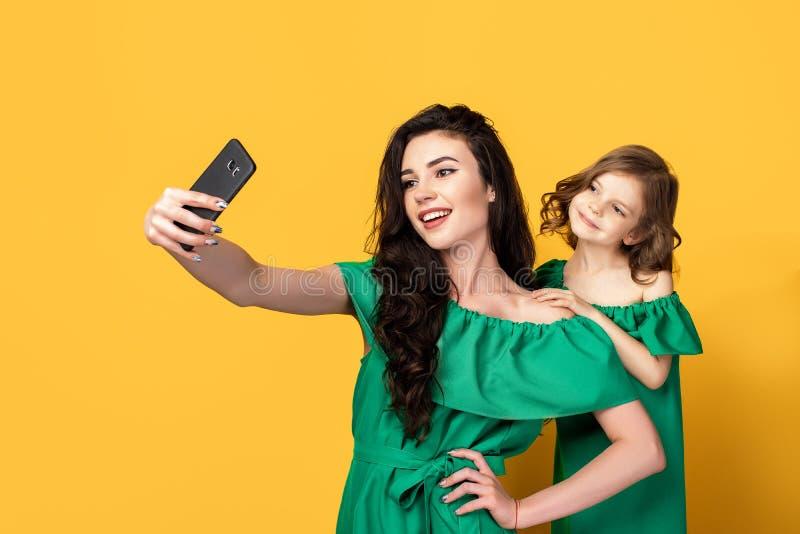 Ehrfürchtige Mutter mit der Tochter, die selfie nimmt stockfotos
