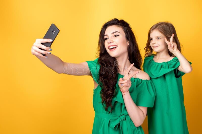 Ehrfürchtige Mutter mit der Tochter, die selfie nimmt lizenzfreie stockfotografie