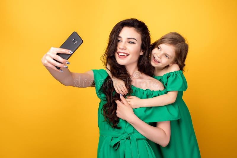 Ehrfürchtige Mutter mit der Tochter, die selfie nimmt lizenzfreie stockfotos