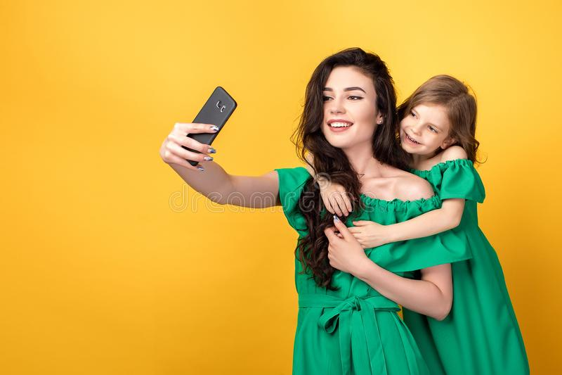 Ehrfürchtige Mutter mit der Tochter, die selfie nimmt stockbild