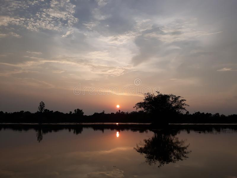 ehrfürchtige Sonne gesetzt nahe von einem netten Bild des Flusses so stockfotos