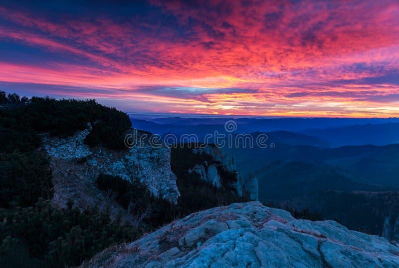 Ehrfürchtiger bunter Sonnenuntergang über den Gebirgshügeln stockfotografie
