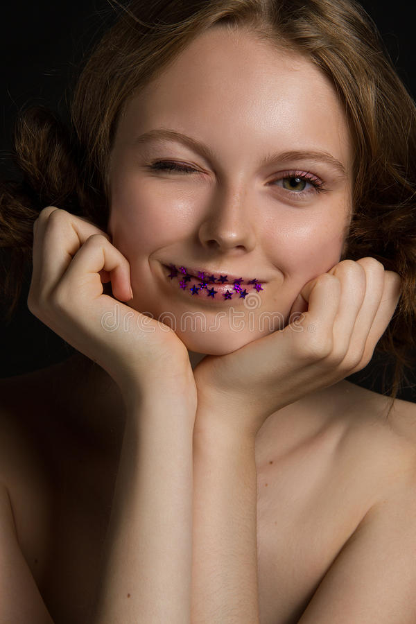 Ehrfürchtiges junges Modell Lächeln und Winks lizenzfreies stockfoto