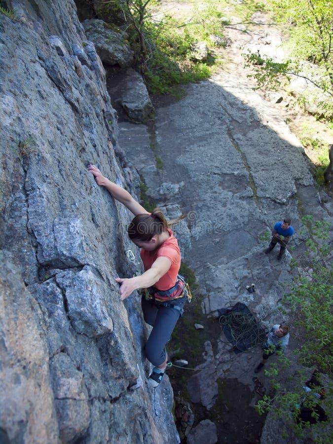 Ehrgeizige Mädchenaufstiege auf einem Felsen stockbild