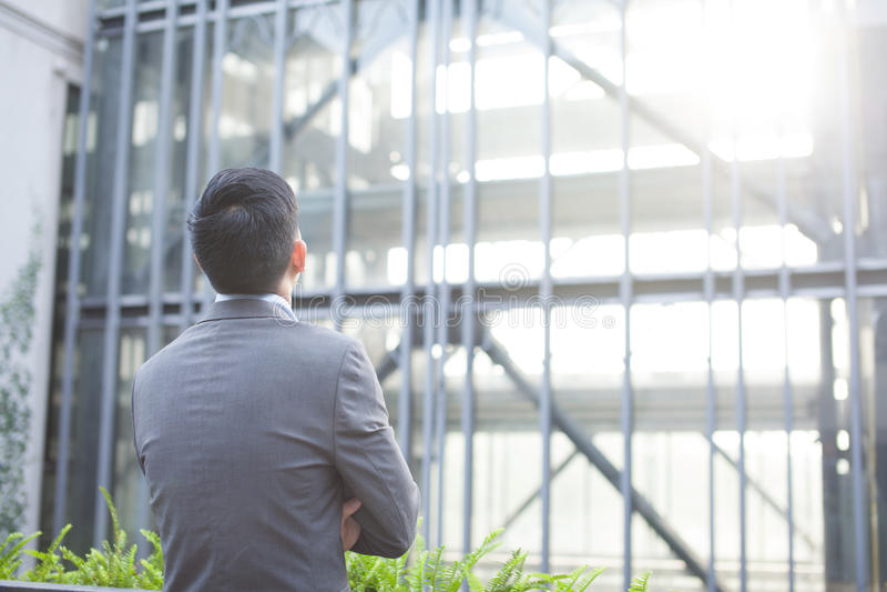 Ehrgeiziger Geschäftsmann vom zurück- schauenden Glasgebäude stockfoto