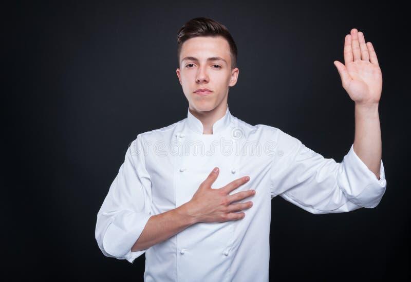 Ehrlicher steigender Koch seine linke Hand und Schwören lizenzfreie stockbilder
