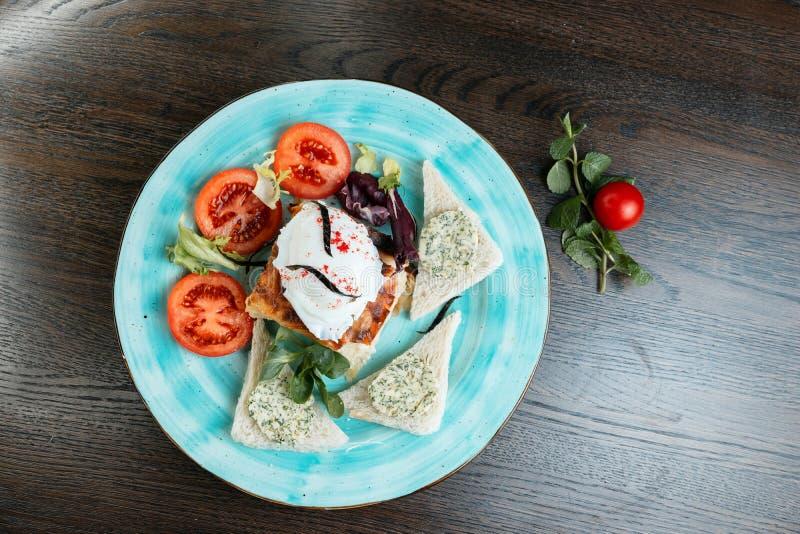 Ei 'poschiert 'mit Scheiben von frischen Tomaten und gebratene Toast mit köstlicher Pastete und Grüns auf einer blauen Platte stockfotos