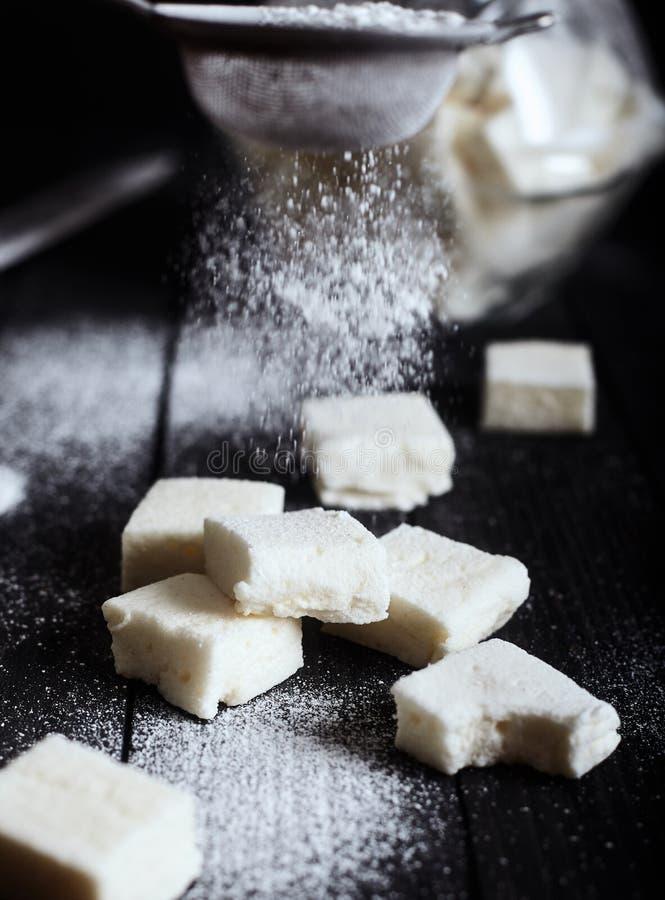 Eibische besprüht mit Zuckerpulver vom Sieb lizenzfreies stockbild