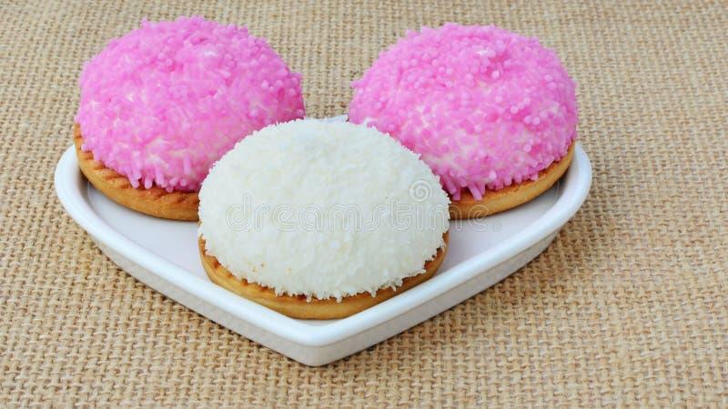 Eibischkekse mit rosa Zucker besprüht und zerriss Kokosnuss stockfotos
