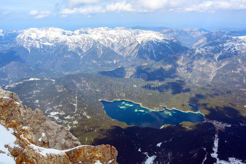 Eibsee lake between the snow covered mountains near Garmisch Partenkirchen, aerial view under a blue sky with clouds, Bavarian. Alps, Germany, Austria, copy royalty free stock photo