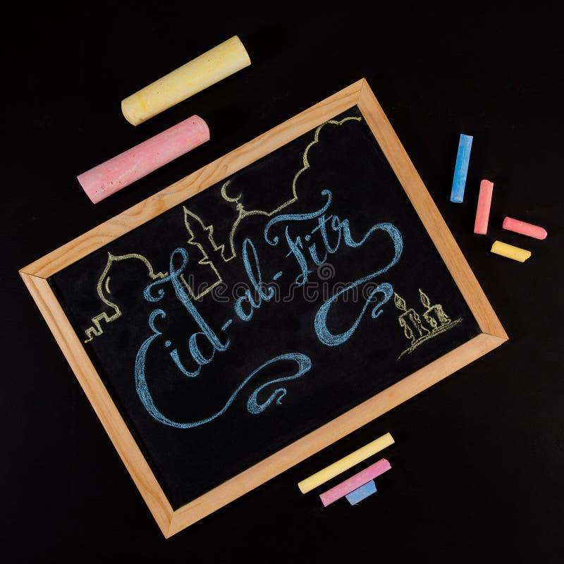 Eid al Fitr-groethand met kleurrijk krijt op bord wordt geschreven - hoogste mening die royalty-vrije stock afbeelding