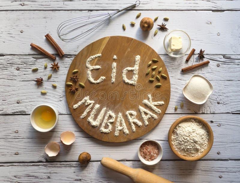 Eid Mubarak - islamisches Feiertagswillkommensphrase ` glückliches Feiertag `, Gruß aufgehoben Arabischer Küchehintergrund stockbild
