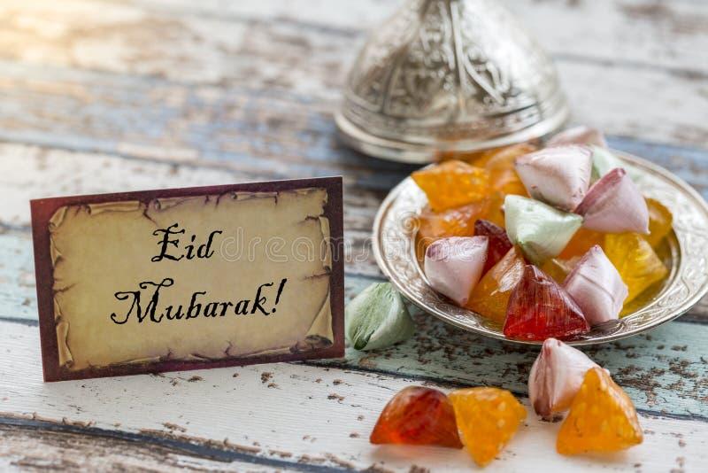 Eid mubarak text on greeting card on vintage table with candies. On metallic plate stock photo