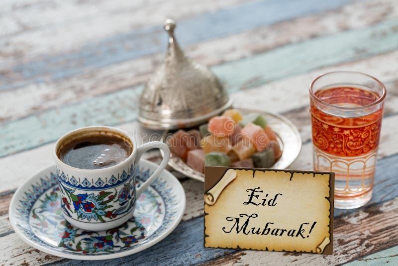 Eid mubarak text på hälsningkort med turkiskt kaffe, fröjder royaltyfria bilder