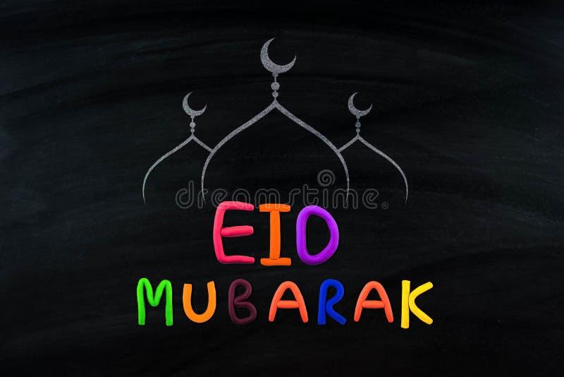 Eid Mubarak traditionell muslimsk hälsning På svart brett royaltyfria foton