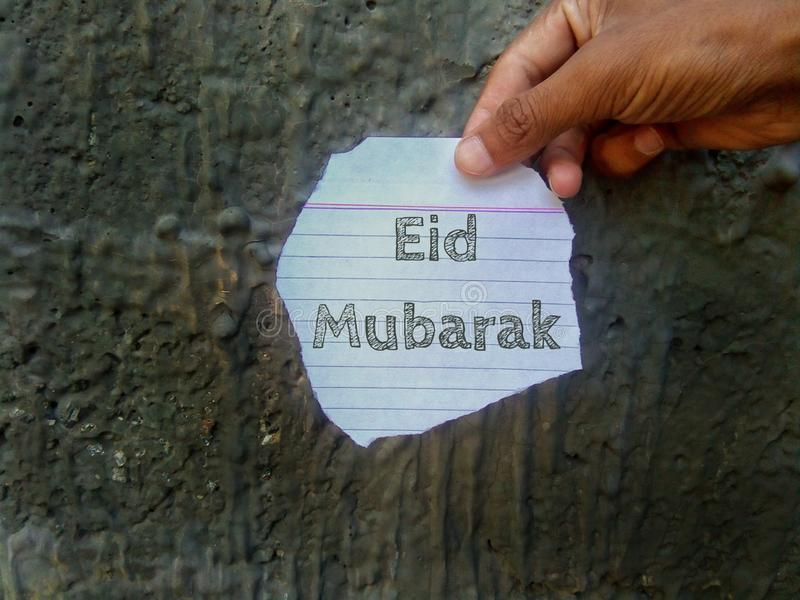 Eid Mubarak wishes written on a piece of paper holding in hand. Eid mubarak wishes written piece paper holding hand text  font letter royalty free stock images