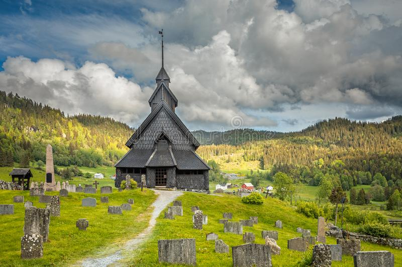 Eidsborg medieval wooden Stave Church and graveyard in front with green forest and cloud sky in the backround, Tokke, Telemark royalty free stock photo