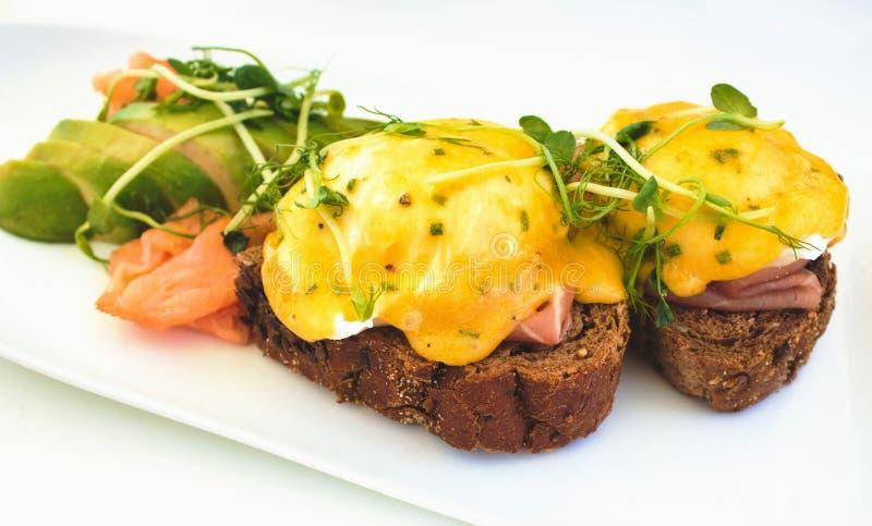 Eier Benedict auf Schwarzbrottoast mit geräuchertem Lachs und Avocado stockfotografie